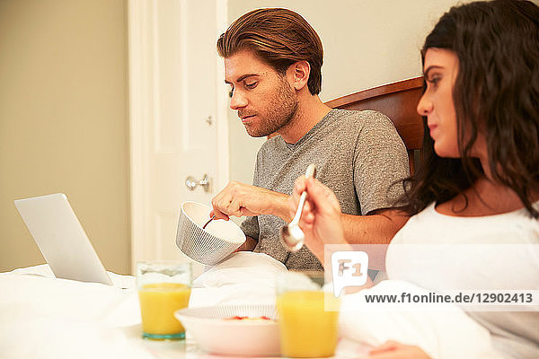 Couple using laptop while having fruit and orange juice breakfast in bed