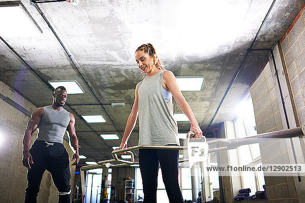 Trainer watching female client lift barbell in gym