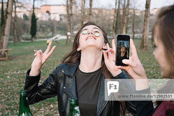 Frau fotografiert einen Freund  der Flaschenverschlüsse auf den Wangen balanciert