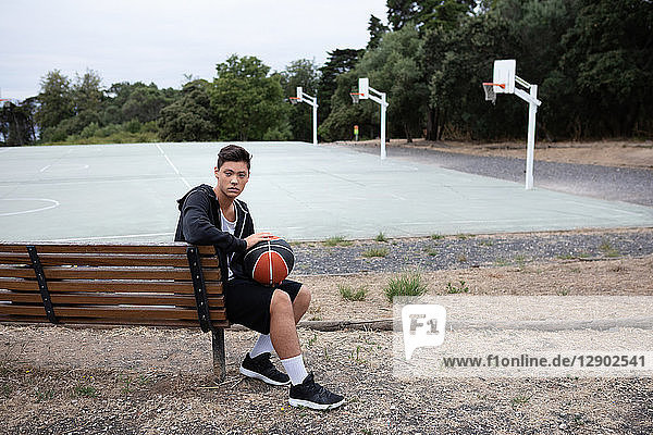 Male teenage basketball player sitting on park bench by basketball court  portrait