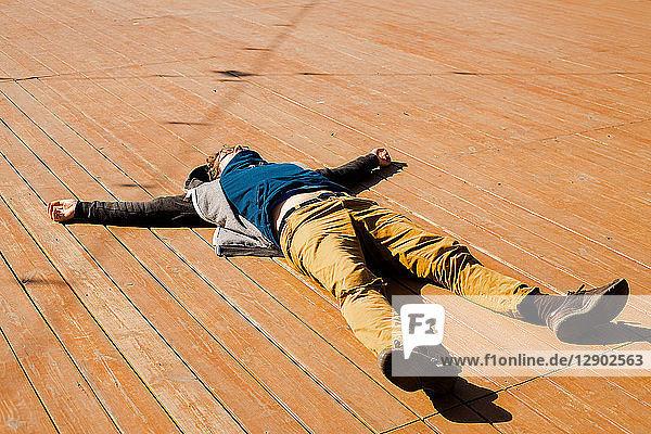 Mann entspannt sich auf Holzterrasse