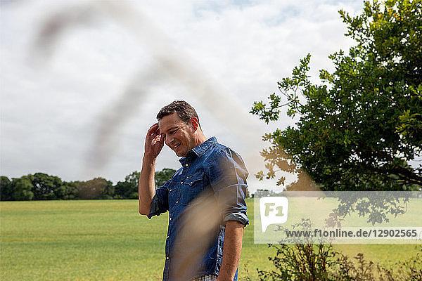Reifer Mann neben ländlichem Feld