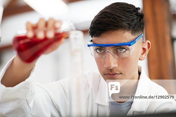 Student gießt Probe in Flasche im Labor