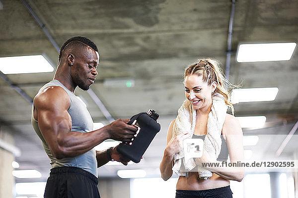 Trainer und Klientin im Gespräch im Fitnessstudio