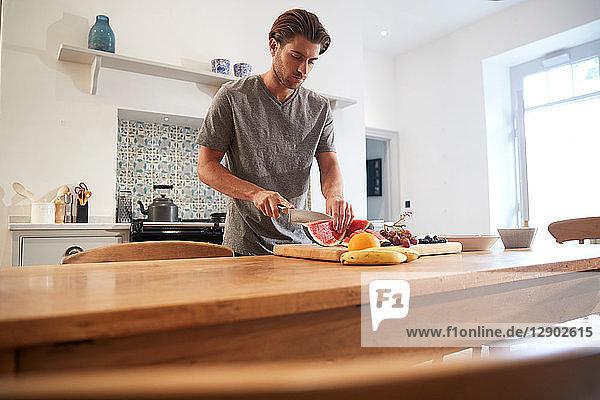 Young man slicing fresh watermelon at kitchen table
