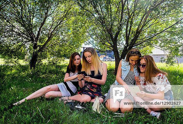 Freundinnen entspannen sich  nutzen intelligente Geräte im Stadtpark