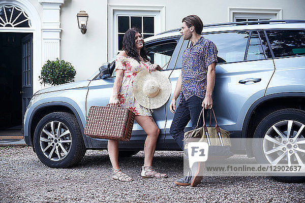 Couple with suitcases leaning against car outside hotel front door