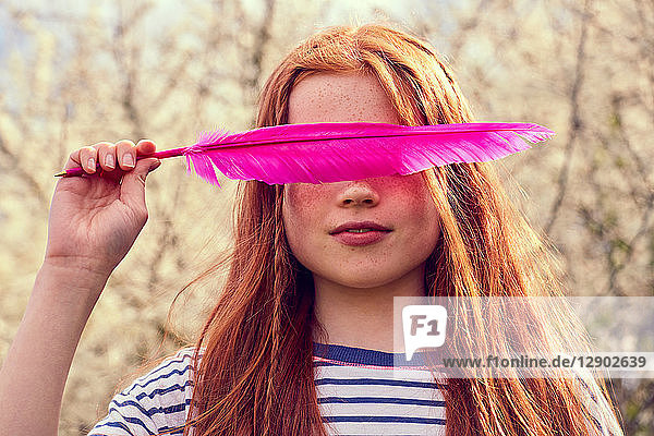 Girl obscuring eyes with pink feather