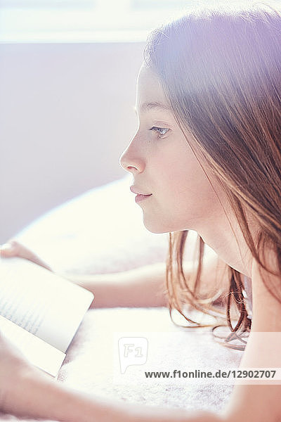 Girl reading book and day dreaming