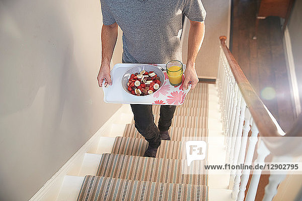 Young man carrying breakfast tray upstairs  neck down