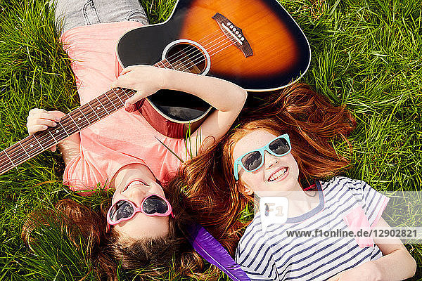 Girls playing guitar on grass