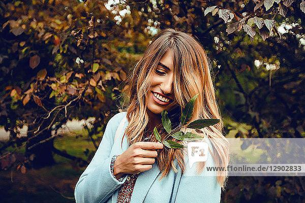 Frau mit langen blonden Haaren hält Blätterzweig im Park  Porträt