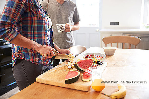 Couple slicing fresh fruit at kitchen table  mid section