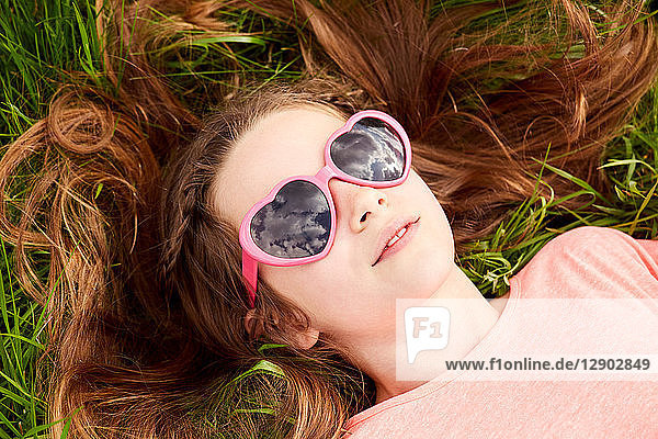 Girl with heart shaped sunglasses lying on grass