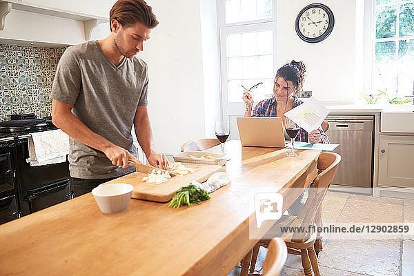 Man preparing vegetables at kitchen table  girlfriend using laptop