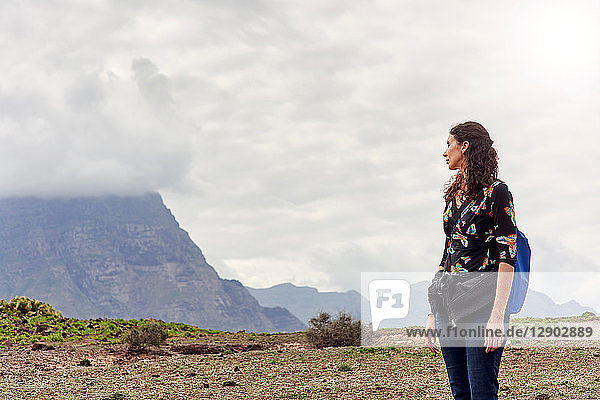 Woman looking out toward low cloud over mountains  Las Palmas  Gran Canaria  Canary Islands  Spain