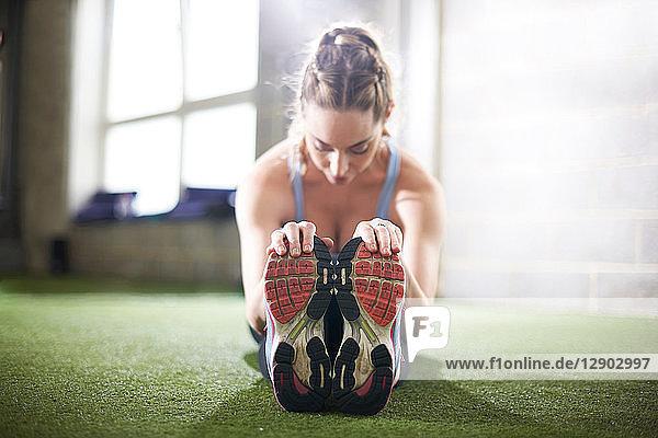 Frau macht Dehnungsübungen im Fitnessstudio