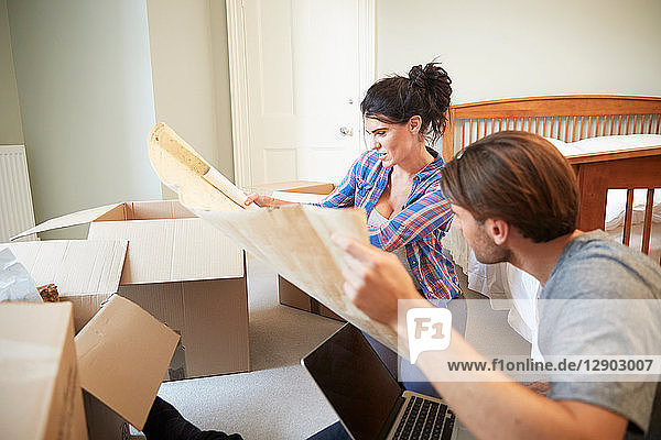 Couple reading blueprint layout in new home