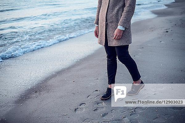 Junge Frau geht am Strand spazieren  hinterlässt Fußspuren im nassen Sand  niedriger Abschnitt