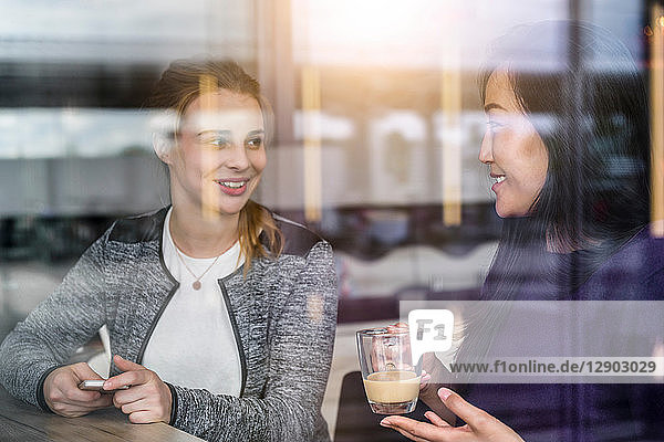 Zwei Studentinnen trinken Kaffee am Fensterplatz eines Cafés