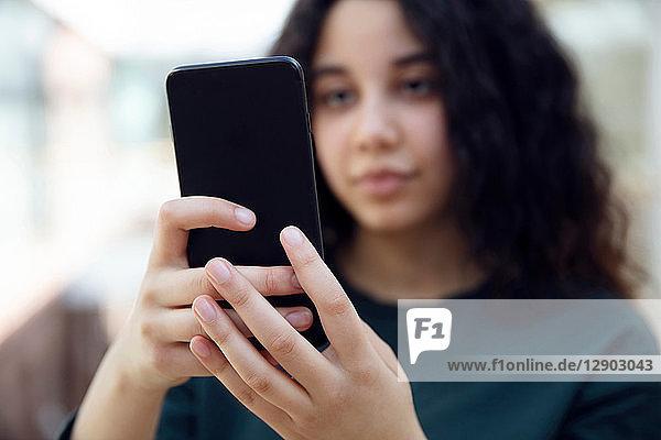 Highschool-Mädchen im Schulflur mit Blick auf Smartphone