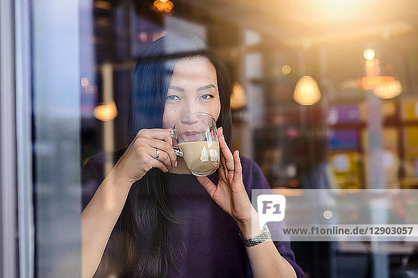 Mid adult woman drinking coffee in cafe window seat  portrait