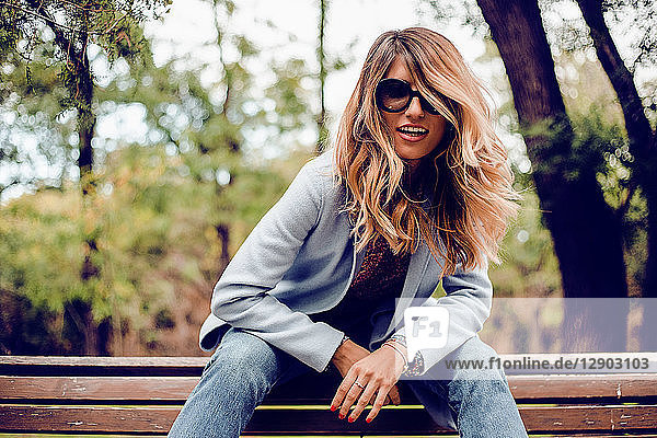 Stilvolle Frau mit langen blonden Haaren und Sonnenbrille auf Parkbank sitzend  Porträt