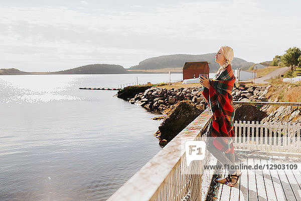 Frau genießt Morgengetränk auf Balkon am Meer,  Halifax,  Kanada