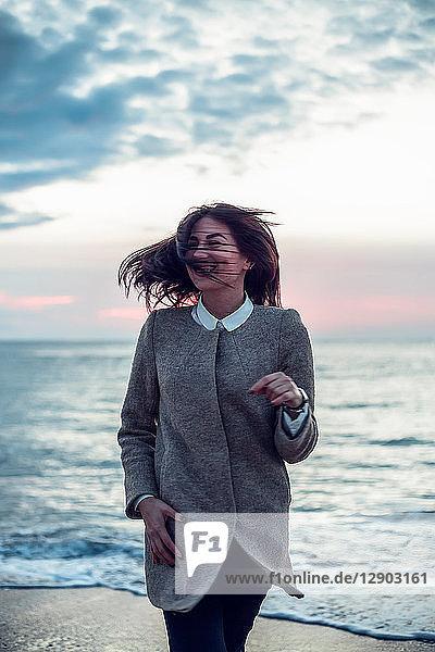 Porträt einer jungen Frau am Strand stehend  mit dem Rücken zum Ozean  der Wind weht ihr Haar  lächelnd