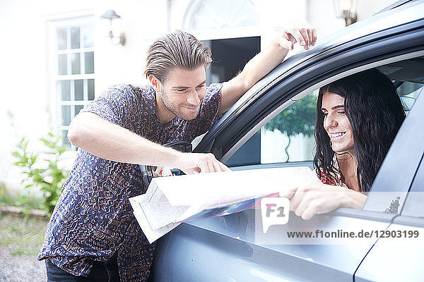 Couple in parked car outside front door looking at folding map