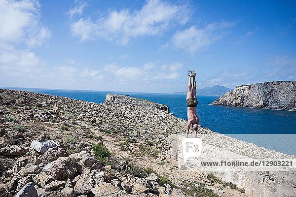 Mann macht Handstand auf der Bergkuppe  Iglesias  Sardinien  Italien
