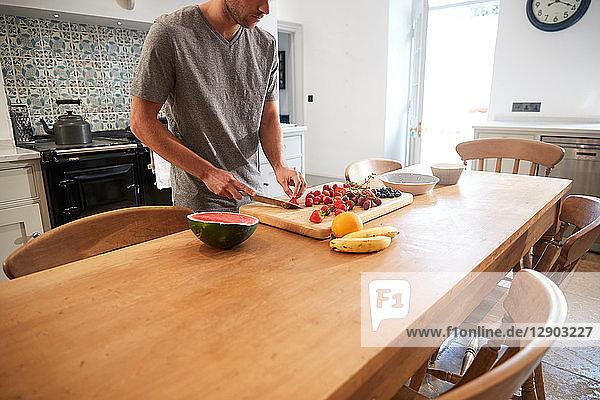 Young man slicing fresh fruit at kitchen table