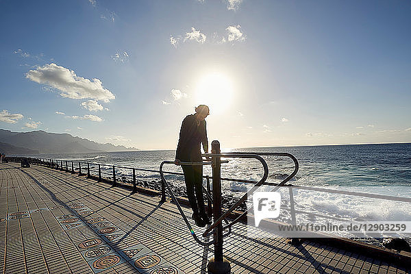 Woman using outdoor exercise machine on promenade  Las Palmas  Gran Canaria  Canary Islands  Spain