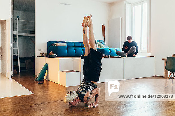 Woman practising yoga at home  friend in background
