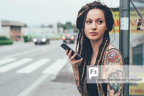 Frau benutzt Mobiltelefon am Straßenrand