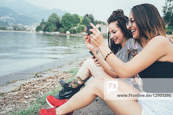 Freundinnen mit Mobiltelefon am Strand