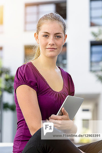 Young woman with digital tablet in park