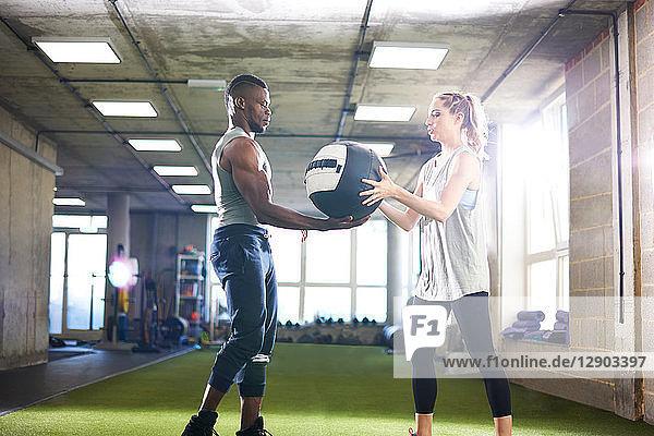 Trainer übergibt Medizinball an Klientin im Fitnessstudio