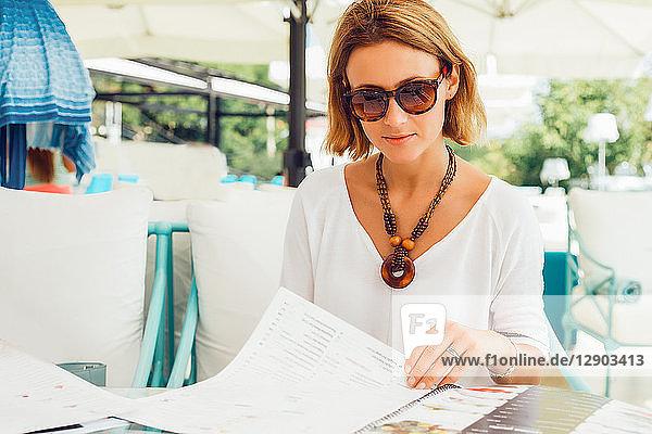 Frau liest Menü auf der Terrasse