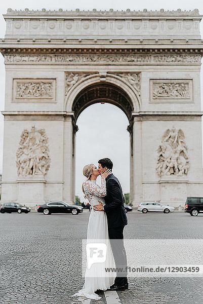 Küssende Braut und Bräutigam  Triumphbogen im Hintergrund  Paris  Frankreich