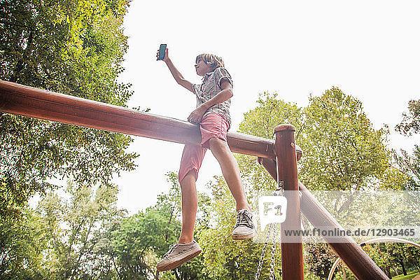 Junge nimmt Selfie auf Spielplatzgeräten mit