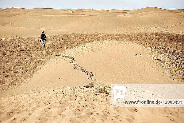 Mature female tourist walking barefoot on sand dune  rear view  Las Palmas  Gran Canaria  Canary Islands  Spain
