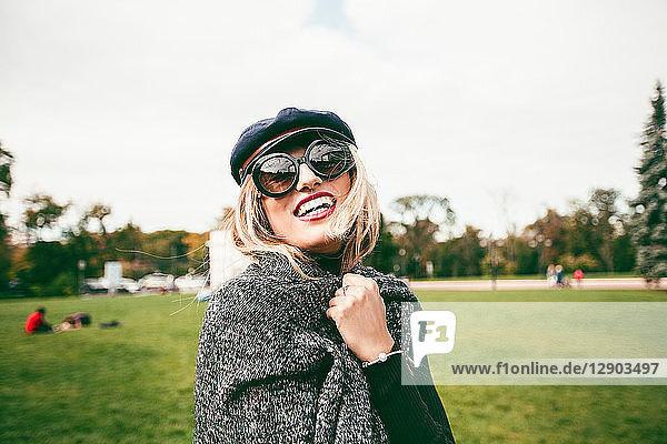 Blond woman wearing sunglasses in park  portrait