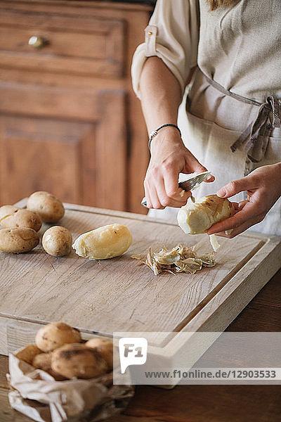 Woman peeling potatoes for gnocchi