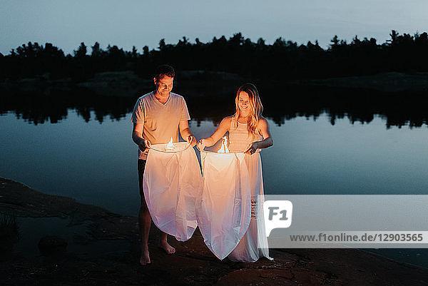 Paar  das Himmelslaternen am See freisetzt  Algonquin Park  Kanada
