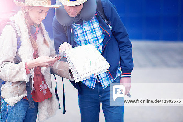 Backpacker couple reading travel documents