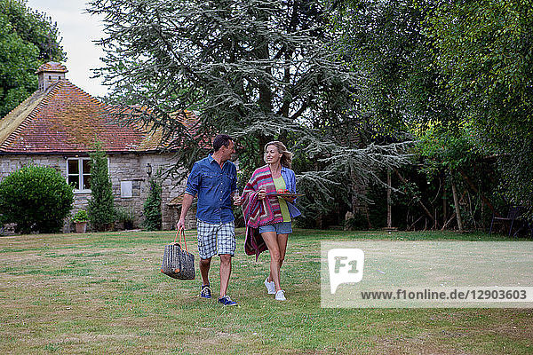 Mature couple strolling across garden lawn with picnic blanket