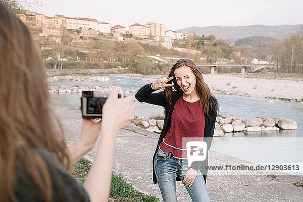 Freundinnen beim Fotografieren am Fluss,  Belluno,  Venetien,  Italien