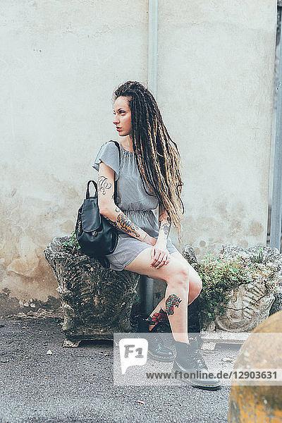 Frau sitzt auf Steinhocker