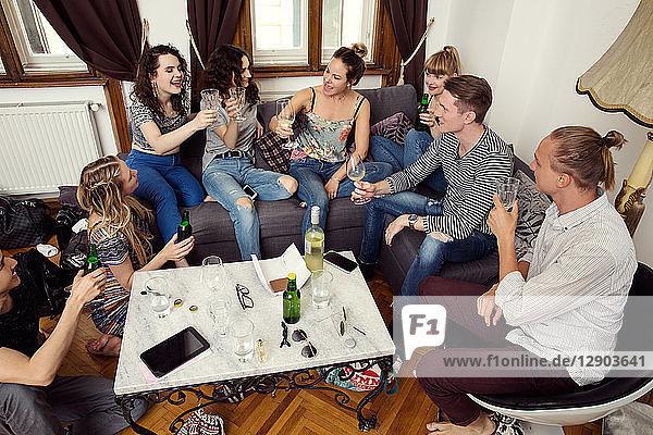 Gruppe von erwachsenen Freunden und Freundinnen  die auf dem Sofa sitzen und einen Toast aussprechen